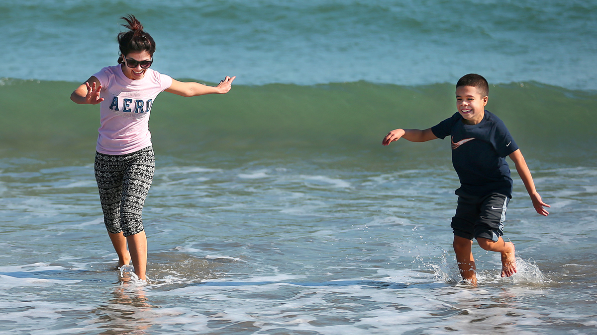 Luiza Narvaz, from Revere, and her 10-year-old son Juan, test the cold water at Revere Beach in Revere, Massachusetts, on Feb. 23, 2017. The weather in Boston was unseasonably warm for February.