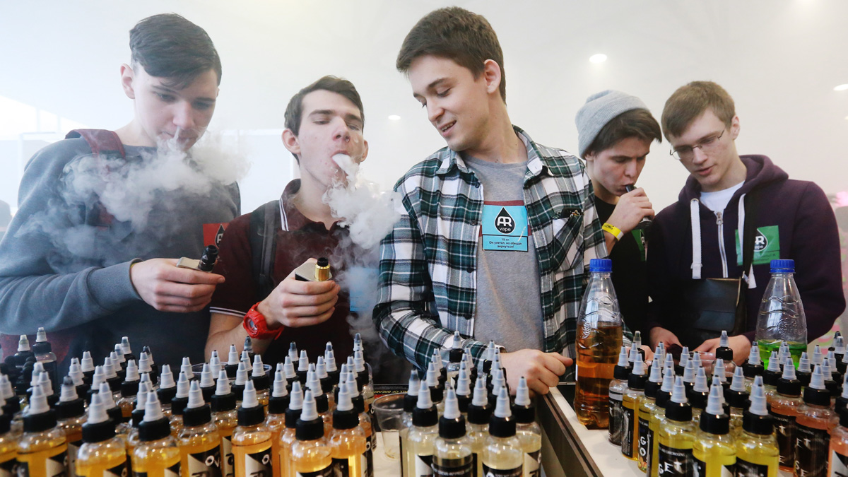 File photo of teenaged visitors smoking electronic cigarettes at the 2017 Vapexpo Spb exhibition of the vape industry at Lenexpo.