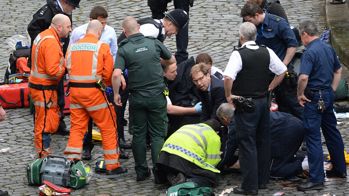 Conservative Member of Parliament Tobias Ellwood (center) helps emergency services attend to a police officer outside the Palace of Westminster, London, after a policeman was stabbed and his apparent attacker shot by officers in a major security incident at the Houses of Parliament.
