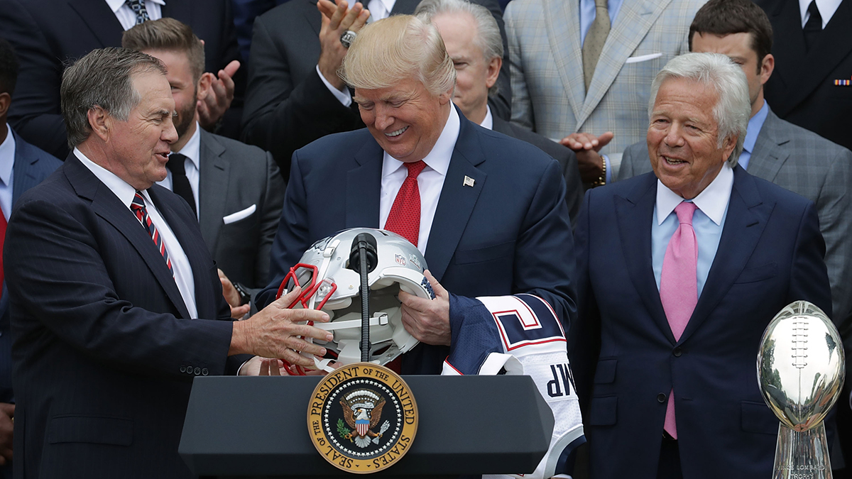 New England Patriots Head Coach Bill Belichick, left, and team owner Robert Kraft at right present a football helmet to President Donald Trump during a celebration of the team's Super Bowl victory on the South Lawn at the White House, April 19, 2017, in Washington, D.C. It was the team's fifth Super Bowl victory since 1960.