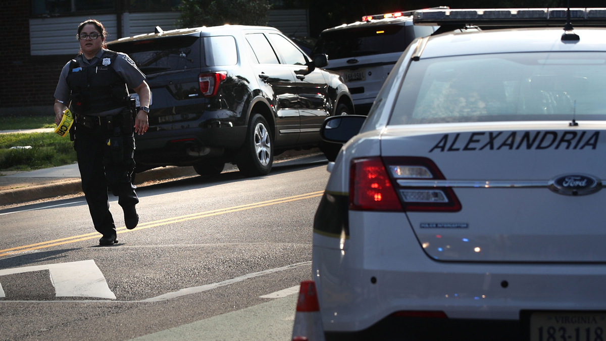 A member of the Alexandria Police runs up the street near the scene of an opened fire June 14, 2017, in Alexandria, Virginia. Multiple injuries were reported from the instance.