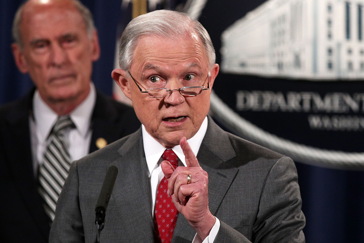 U.S. Attorney General Jeff Sessions speaks as Director of National Intelligence Dan Coats listens during an event at the Justice Department Aug. 4, 2017, in Washington, D.C.