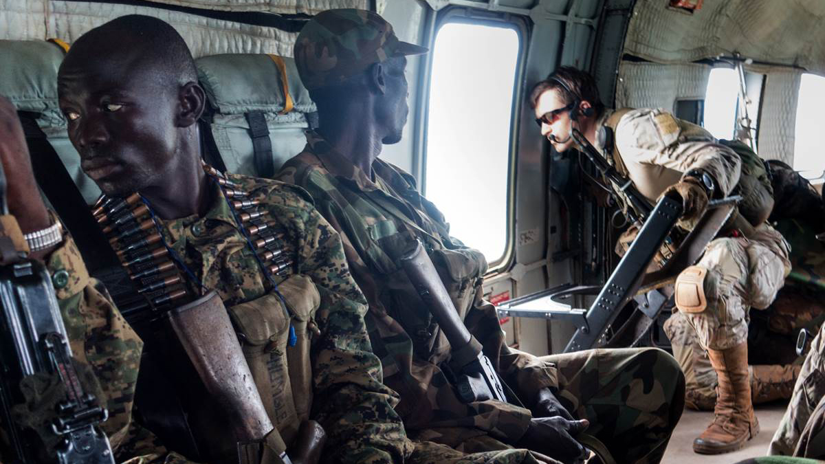 A Green Beret examines a landing zone in the wilderness of central Africa as his team conducts a patrol along with soldiers from the Ugandan People's Defense Force.