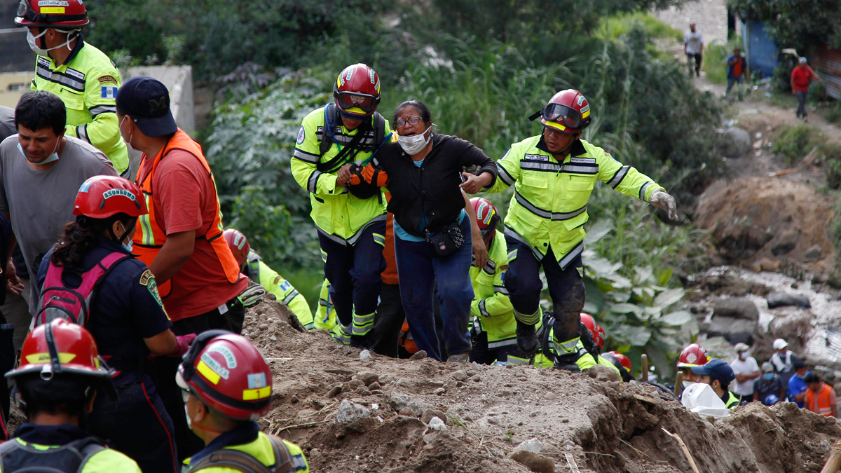 Rescue workers help a woman after she identified two family members who were killed in a mudslide as their bodies are retrieved in Cambray, a neighborhood in the suburb of Santa Catarina Pinula, on the outskirts of Guatemala City, Saturday, Oct. 3, 2015. Rescue workers recovered more bodies Saturday after a hillside collapsed on homes late Thursday, while more are feared still buried in the rubble.
