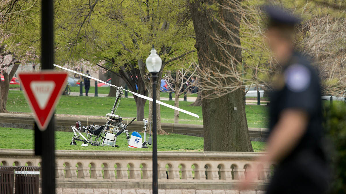 A Capitol Hill police officer looks toward a small helicopter that landed on the West Lawn of the Capitol in Washington, Wednesday, April 15, 2015.