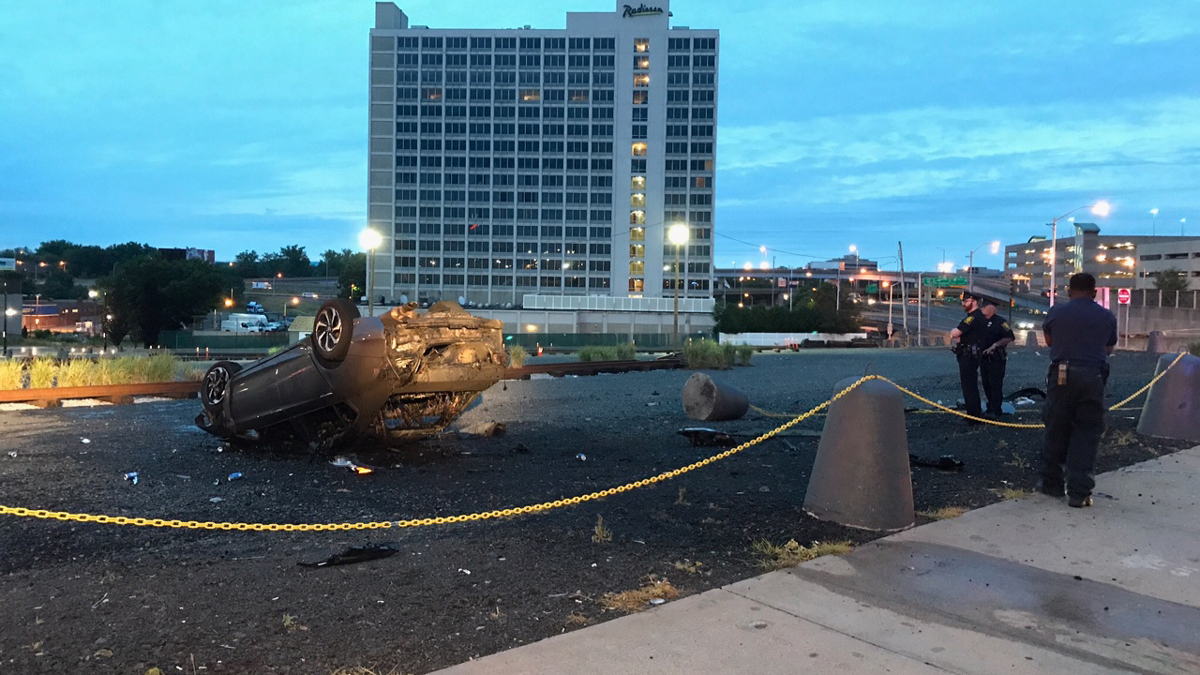 A car traveling down Main Street in Hartford crashed into a pole and a parking lot barricade before flipping over and catching fire early Friday. The driver fled the scene.