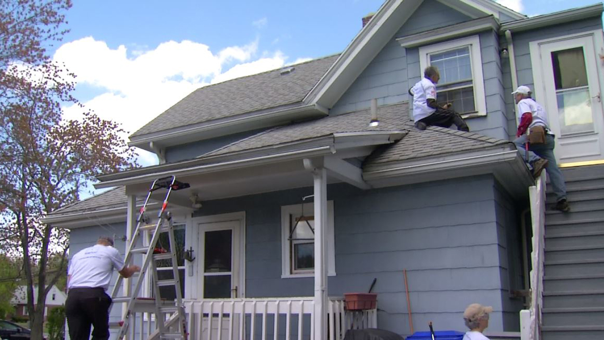 Volunteers work on a home on Elm Street in Enfield on Homefront Day Saturday. The homeowners have lived there since 1952 and said they were grateful for the work being done to keep it safe.