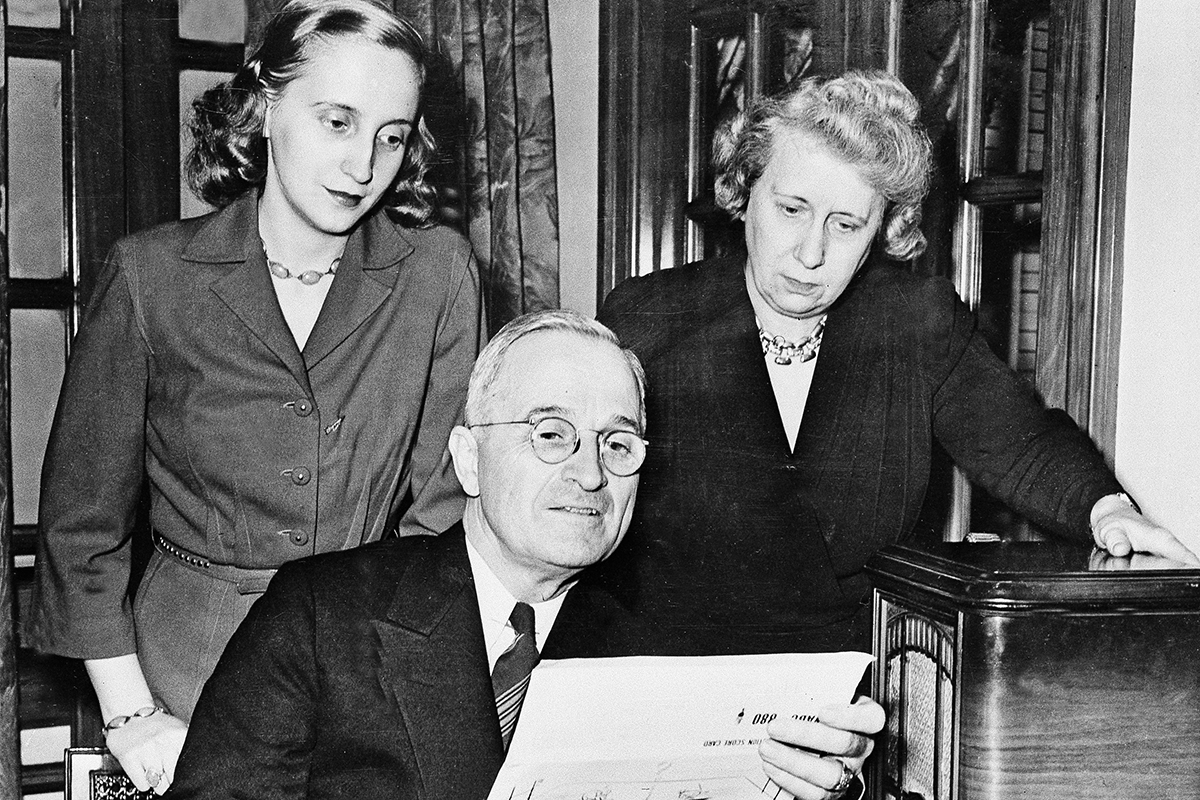 Margaret Truman, left, and her mother Bess look over the shoulder of then-Sen. Harry S. Truman in Kansas City as he makes a chart of election returns heard over the radio, Nov. 7, 1944. The Trumans entered the White House as its first family when Franklin. D. Roosevelt unexpectedly died just 82 days into the fourth term of his presidency.