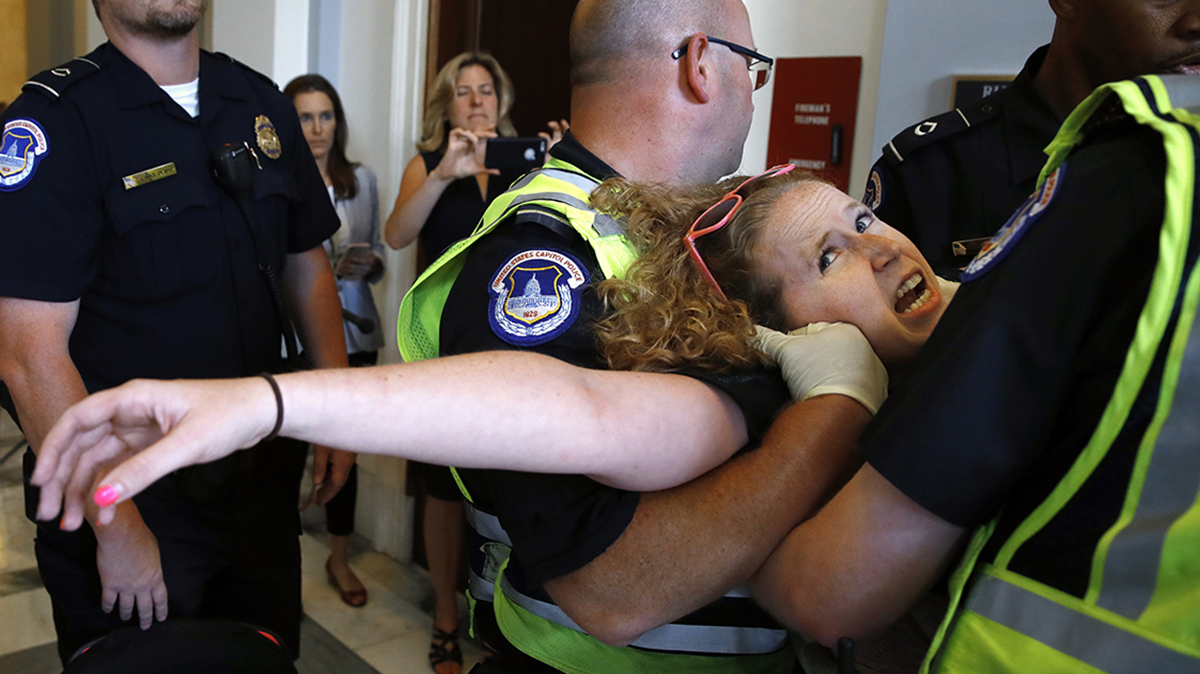 Stephanie Woodward, of Rochester, NY, who has spina bifida and uses a wheelchair, is removed from a sit-in at Senate Majority Leader Mitch McConnell's office as she and other disability rights advocates protest proposed funding caps to Medicaid, Thursday, June 22, 2017, on Capitol Hill in Washington. (AP Photo/Jacquelyn Martin)