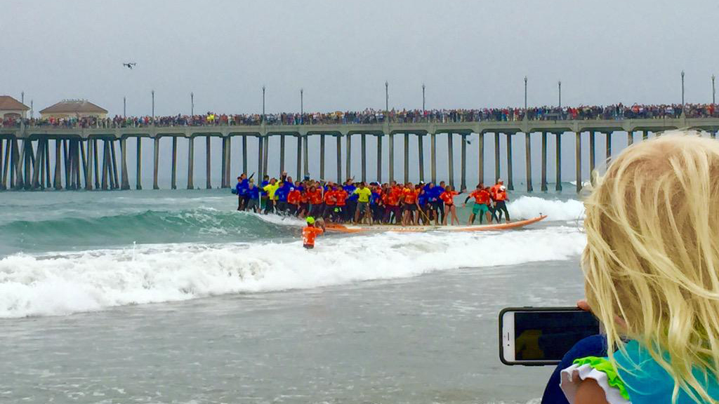 Dozens of surfers ride a 42-foot surfboard in a world-record attempt in Huntington Beach on Saturday, June 20, 2015, in this viewer photo.
