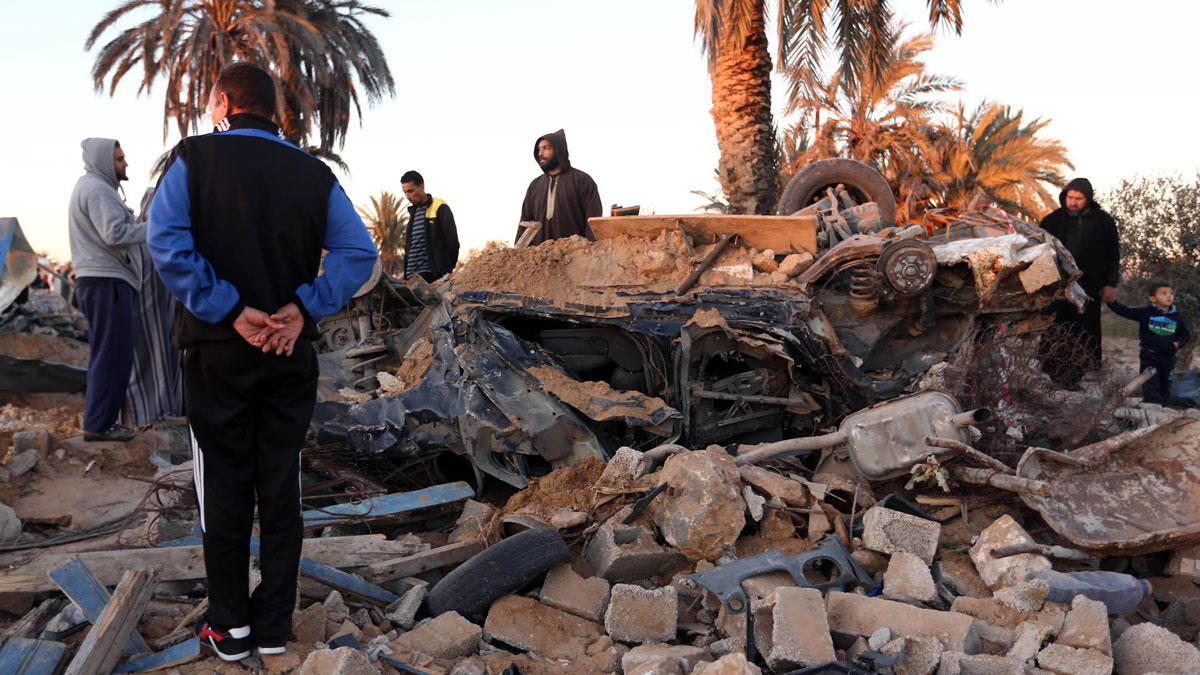 People gather around a damaged area after U.S. warplanes carried out air strikes against Daesh training camp in western Libya in this February 19, 2016, file photo.