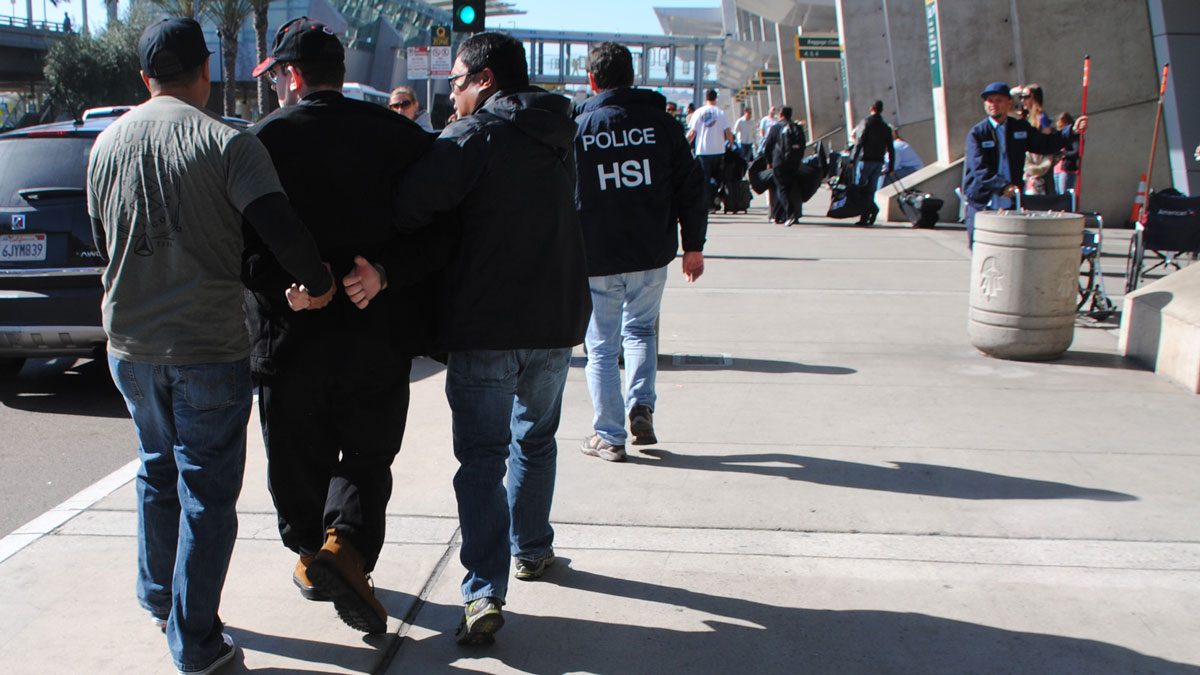 In this Friday, Jan. 29, 2016 photo provided by the U.S. Immigration and Customs Enforcement (ICE), former Columbus, Ohio, seminarian Joel Wright (second from left) is arrested at San Diego's airport in San Diego on federal charges for allegedly seeking to have sex with infant and young girls in Mexico.