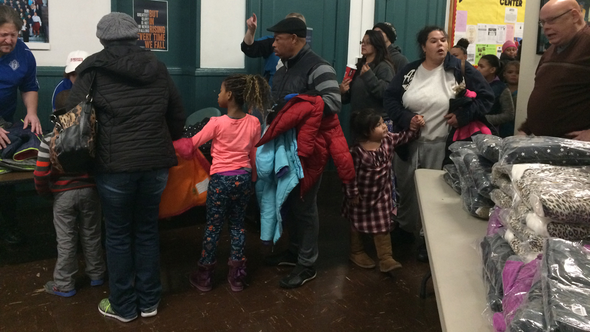 Families wait in line to pick up a coat from the Knights of Columbus at the St. Martin de Porres Academy in New Haven