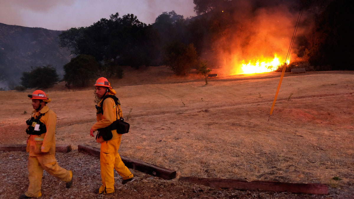 Los Angeles County firefighters approach a brush fire in the foothills outside of Calabasas, Calif. on Saturday, June 4, 2016. A fast-moving brush fire sweeping through hills northwest of downtown Los Angeles has damaged homes and prompted neighborhood evacuations.