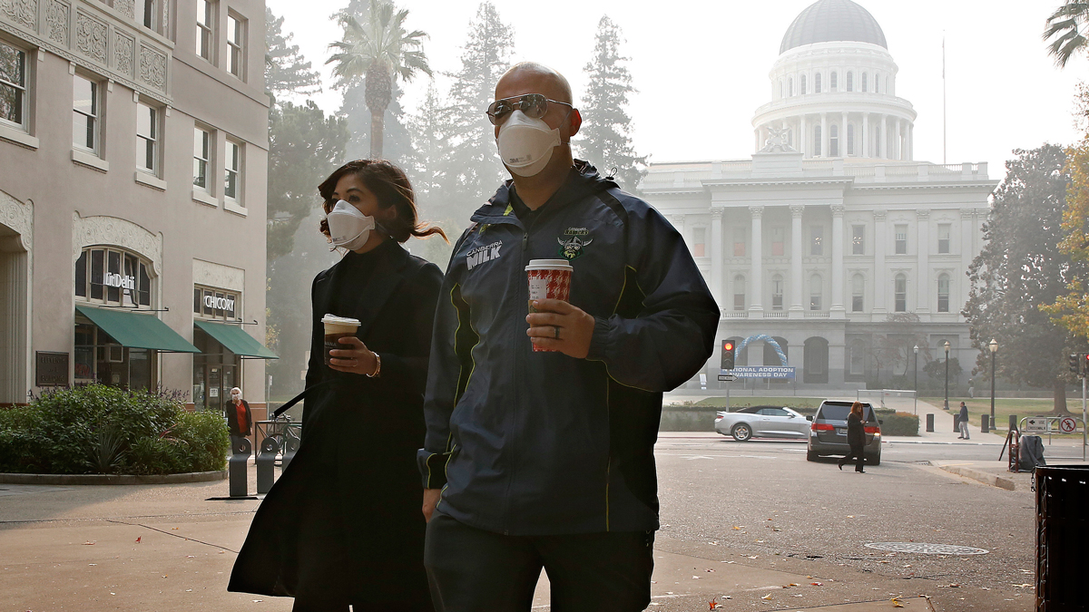 Mattelin Bautista and Stephen Penner don masks to deal with the smoke from the Camp Fire that shrouds the state Capitol Thursday, Nov. 15, 2018, in Sacramento, Calif. Smoke from the blaze that burned through the Butte County city of Paradise is creating a health hazard that experts say could lead to an increase in serious health problems, especially for children and the elderly.