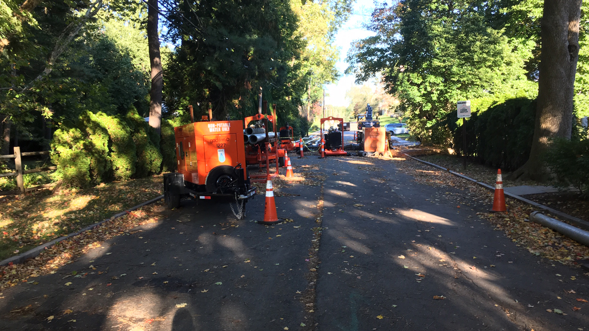 Equipment still lines Linbrook Road in West Hartford more than two weeks after a sewer backup caused water to flood into homes.