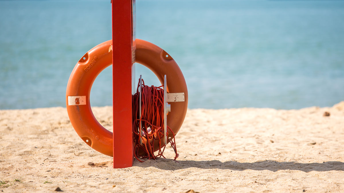 A ring buoy, also known as a lifebuoy, is seen by the seaside.