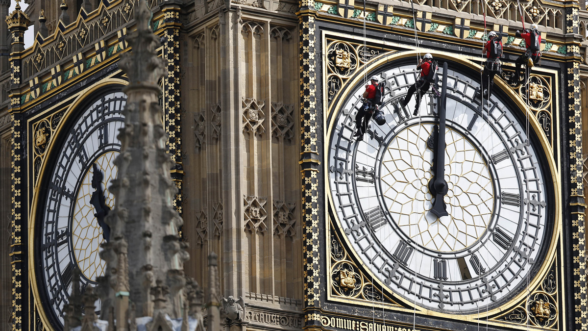In this file photo, workers hang outside the clock face as they clean the Big Ben clock-tower of the Houses of Parliament in London, Monday, Aug. 18, 2014.