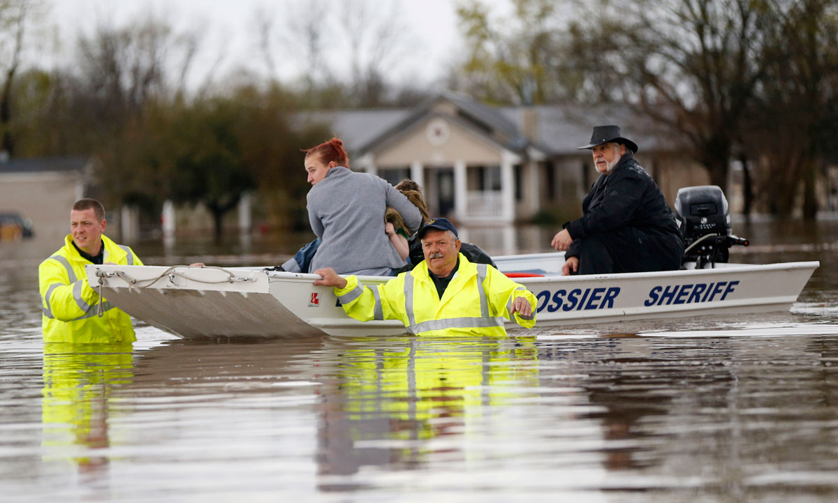 Sarah Yatcko, left, holds her son Tucker Neal as they are evacuated by boat with her father Jim Yatcko, by Bossier County Sheriff personnel during rising floodwaters in Bossier Parish, La., Thursday, March 10, 2016.