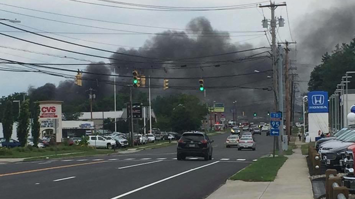 Large amounts of smoke from a junk yard fire visible above the street in Milford.
