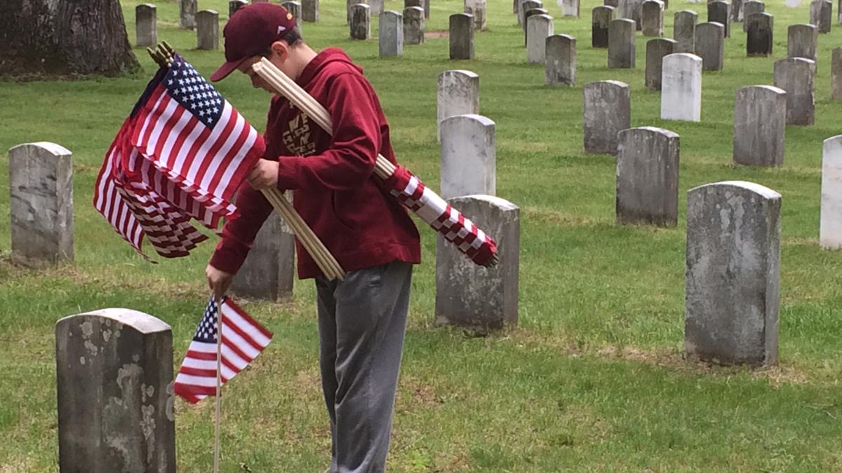 Volunteers placed flags on thousands of veterans' graves in East Hartford Saturday.