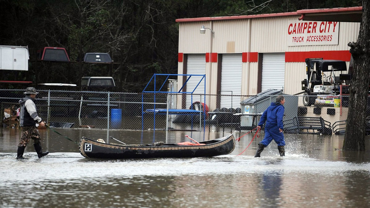 A pair of men pull a canoe past a flooded business along U.S. Highway 49 in Hattiesburg, Mississippi, Saturday, March 12, 2016, after more than 10 inches of rain fell in the Pine Belt area over the last two days.