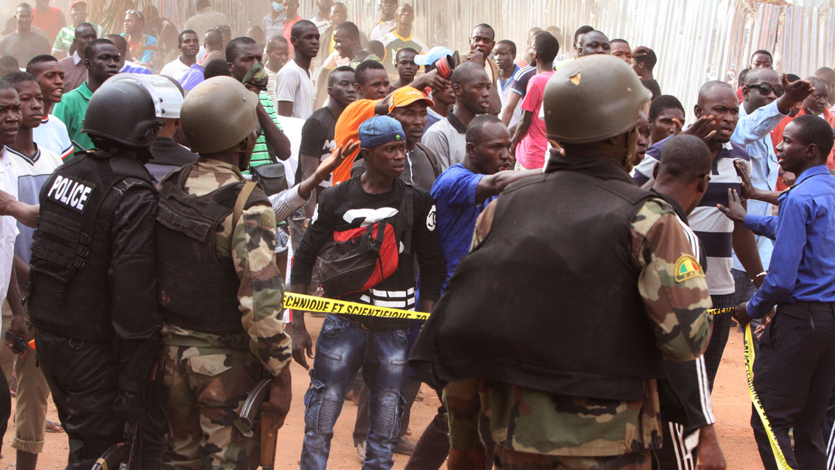 Mali troops try to control a crowd of onlookers near the  Radisson Blu hotel, after an attack by gunmen on the hotel in Bamako, Mali, Friday, Nov. 20, 2015. Islamic extremists armed with guns and grenades stormed the luxury Radisson Blu hotel in Mali's capital Friday morning, and security forces worked to free guests floor by floor.