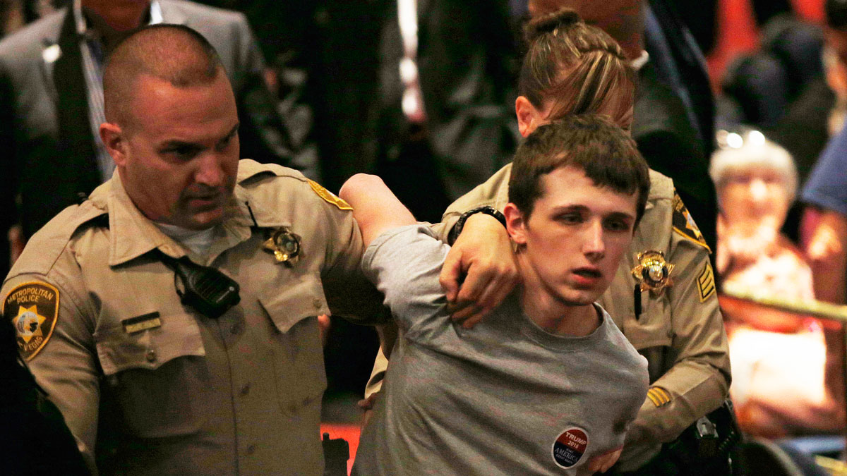 In this June 18, 2016, photo, police remove Michael Sandford as Republican presidential candidate Donald Trump speaks at the Treasure Island hotel and casino in Las Vegas. Sandford, a British man accused of trying to take a police officer's gun and kill the presumptive Republican presidential nominee pleaded not guilty to the charges in federal court on July 6, 2016.