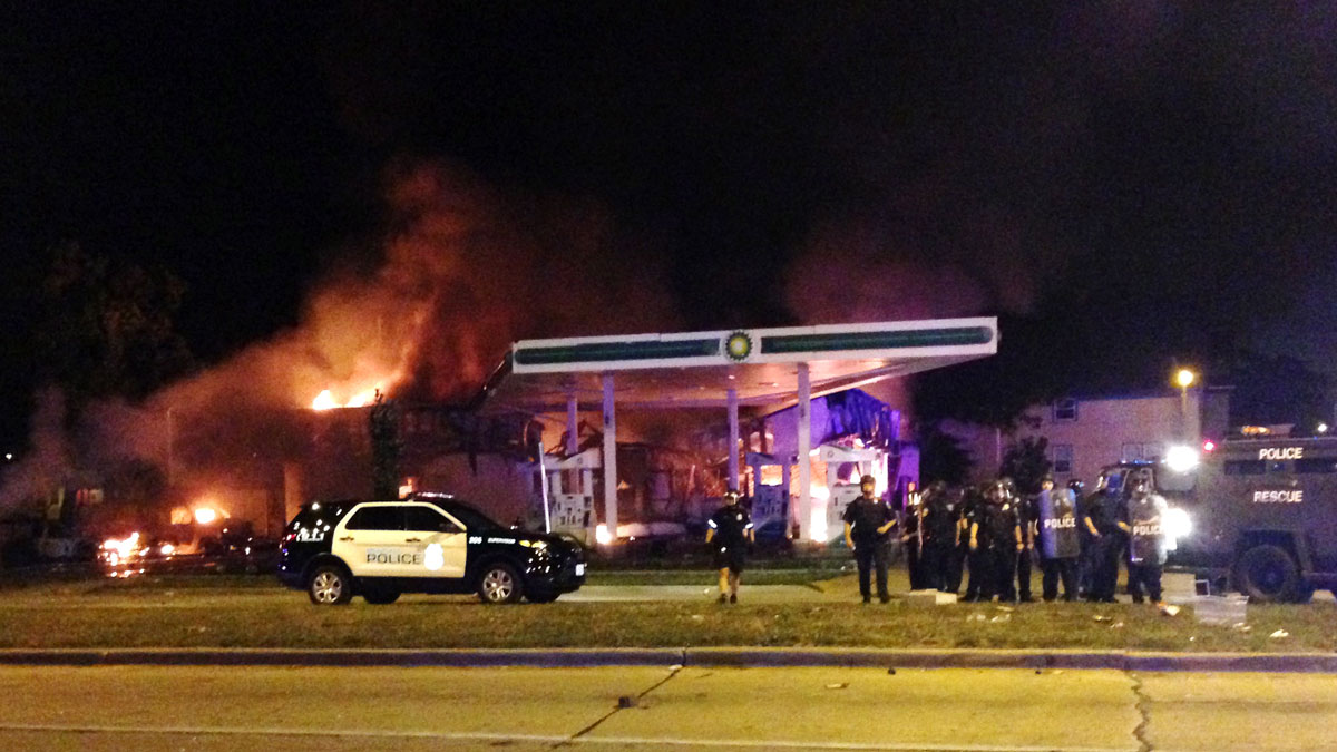 Authorities respond near a burning gas station as dozens of people protest following the fatal shooting of a man in Milwaukee, Saturday, Aug. 13, 2016. A crowd of protesters skirmished with police Saturday night in the Milwaukee neighborhood where an officer shot and killed a man after a traffic stop and foot chase earlier in the day, setting fire to a police car and torching a gas station.