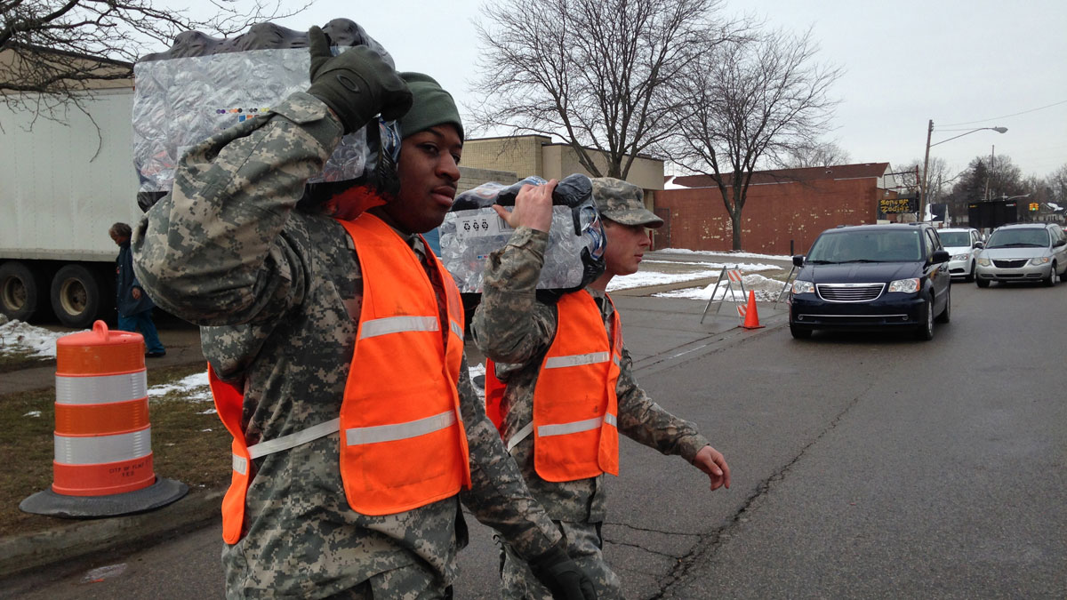 National Guardsmen carry water to a resident's car in Flint, Mich., on Friday, Jan. 22, 2016. Residents across the city have been forced to rely on bottled water after leached pipes brought lead and other dangerous substances into their homes.