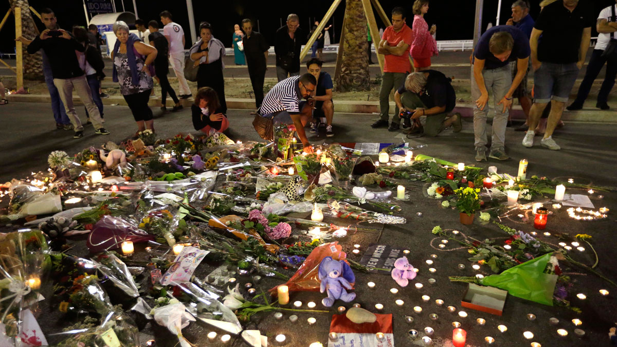 People lay flowers and light candles to honor the victims of an attack, near the area where a truck mowed through revelers in Nice, southern France, July 16, 2016. A large truck mowed through revelers gathered for Bastille Day fireworks in Nice, killing score of people and sending people fleeing into the sea as it bore down for more than a mile along the Riviera city's famed waterfront promenade.
