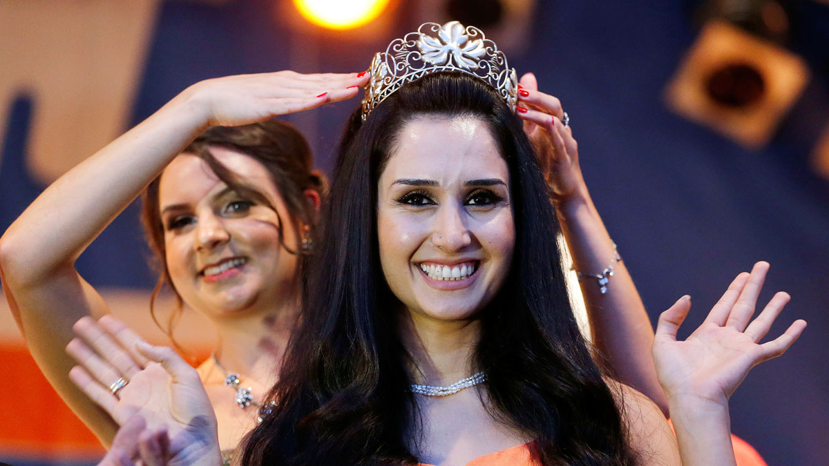 Being crowned by her predecessor, 26-year-old former Syrian refugee Ninorta Banho is crowned, becoming the first former refugee in Germany to be crowned Wine Queen of Trier, in the town of Trier, southern Germany on Aug. 3, 2016. Banho was a Syrian refugee who fled to Germany in 2012.
