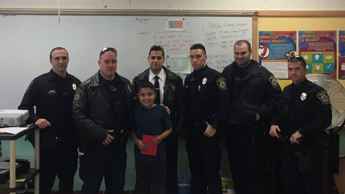 North Haven police officers presented Christian Mercado with a $250 gift card at the North Haven Middle School on Wednesday.