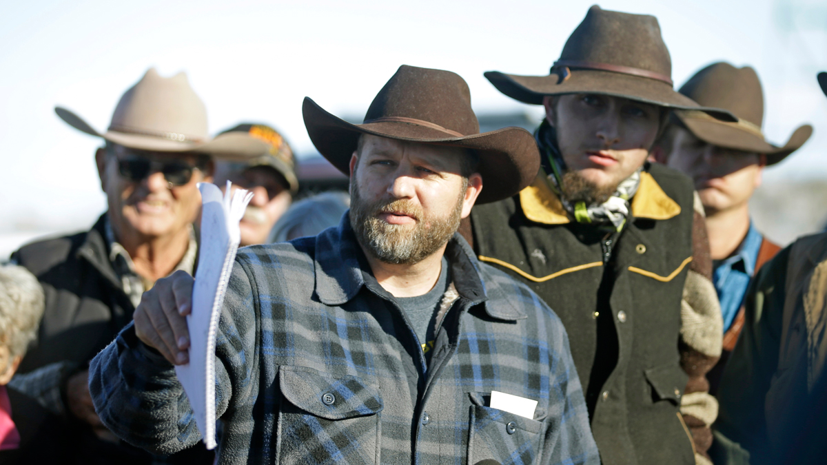 Ammon Bundy, center, speaks with a reporter at a news conference at Malheur National Wildlife Refuge Friday, Jan. 8, 2016, near Burns, Ore. Bundy, the leader of an armed group occupying the national wildlife refuge to protest federal land management policies, said Friday he and his followers are not ready to leave even though the sheriff and many locals say the group has overstayed their welcome.