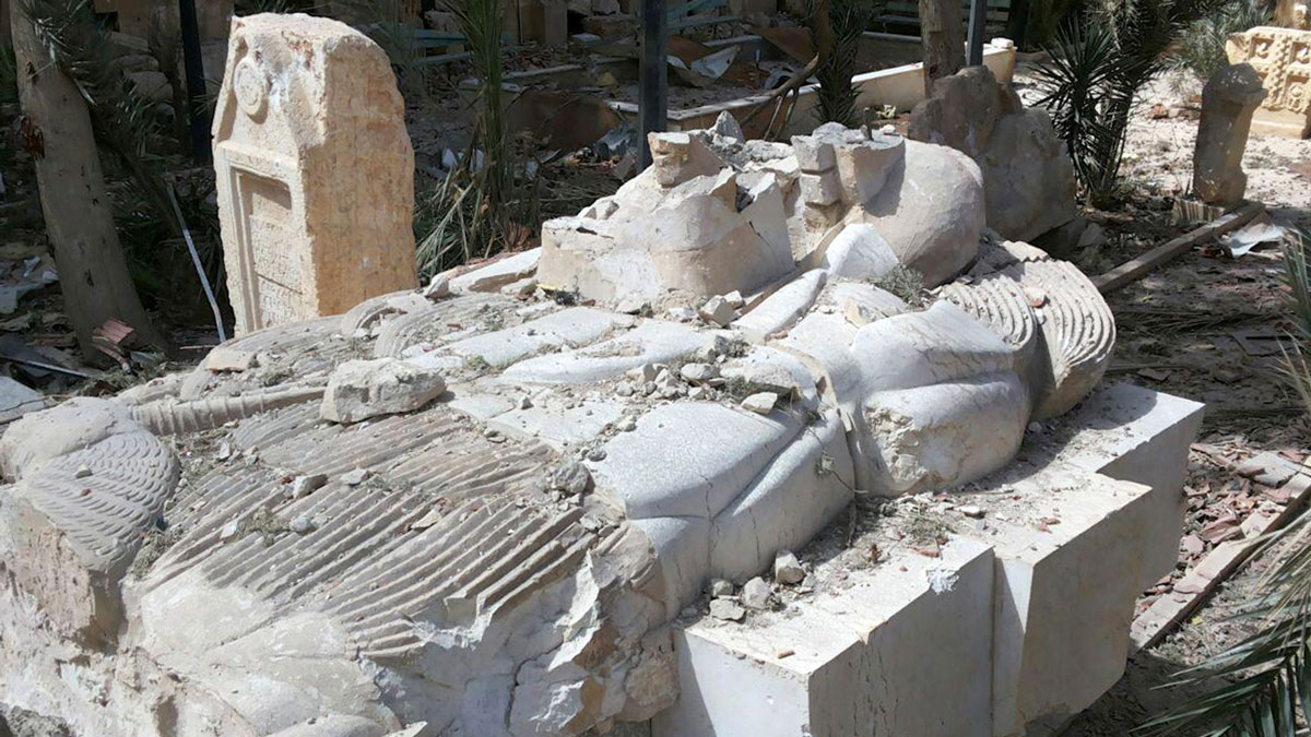 This photo released on Sunday March 27, 2016, by the Syrian official news agency SANA, shows a destroyed statue outside the damaged Palmyra Museum, in Palmyra city, central Syria.