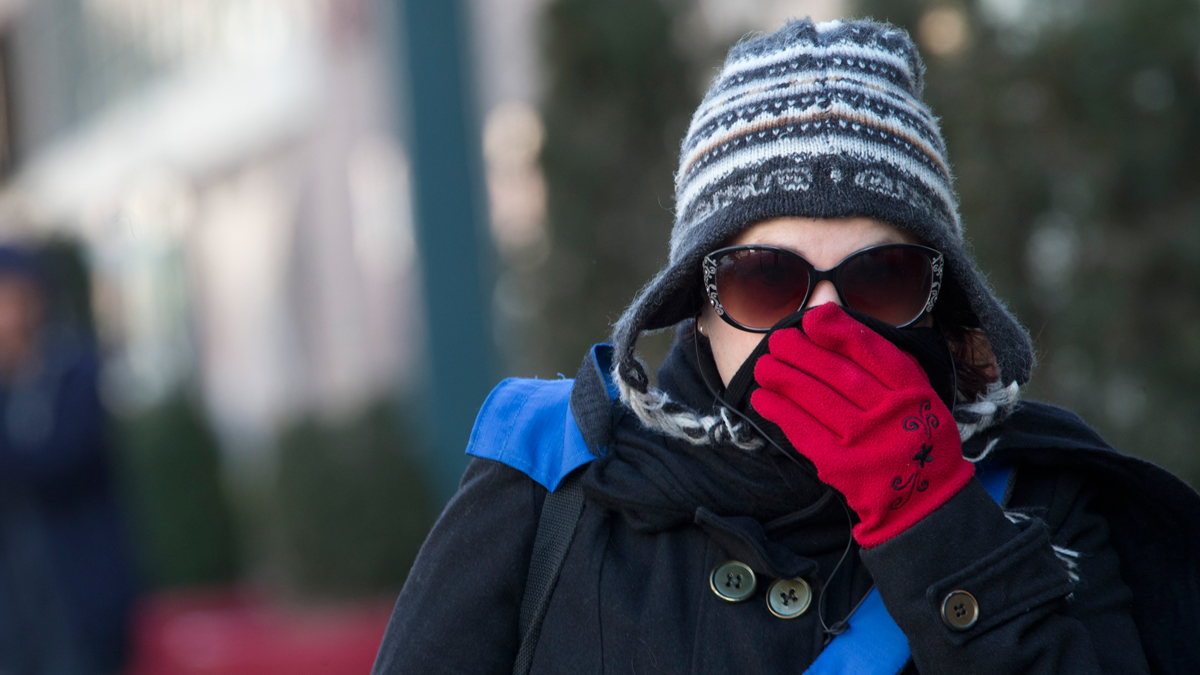 A woman lifts her scarf up in front of her nose to shield from the cold air, Friday, Feb. 12, 2016, in New York.