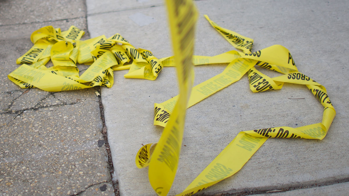 Police tape is pictured on the ground near a crime scene.