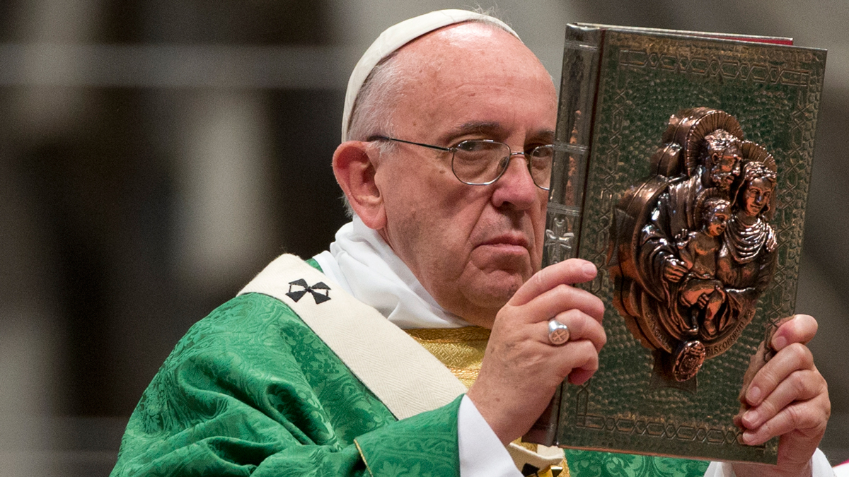 Pope Francis raises the book of the Gospels as he celebrates the opening Mass of the Synod of bishops, in St. Peter's Basilica at the Vatican, Sunday, Oct. 4, 2015.