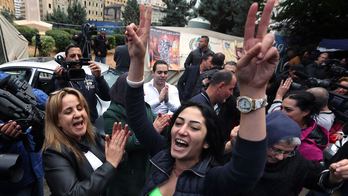 Families of soldiers and policemen who were kidnapped by militants from the Islamic State group and al-Qaida's branch in Syria, the Nusra Front, cheer after following news that their sons were being released, in front of tents set up for a protest in downtown Beirut, Lebanon, Tuesday, Dec. 1, 2015. A group of Lebanese soldiers held captive since August 2014 were being released Tuesday as part of a swap deal.