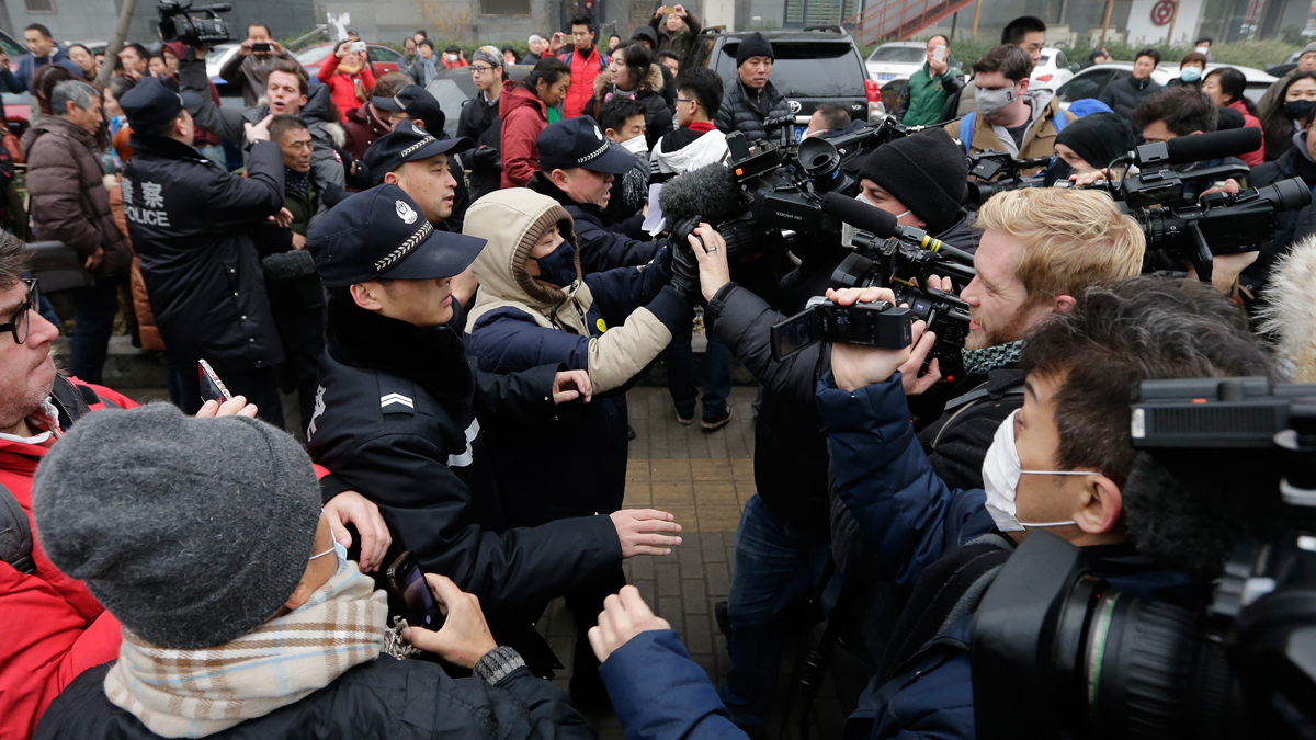 Police officers push away foreign journalists covering rights lawyer Pu Zhiqiang's trial at the Beijing Second Intermediate People's Court in Beijing, Monday, Dec. 14, 2015. Pu went on trial Monday on charges of provoking trouble with commentaries on social media that were critical of the ruling Communist Party.
