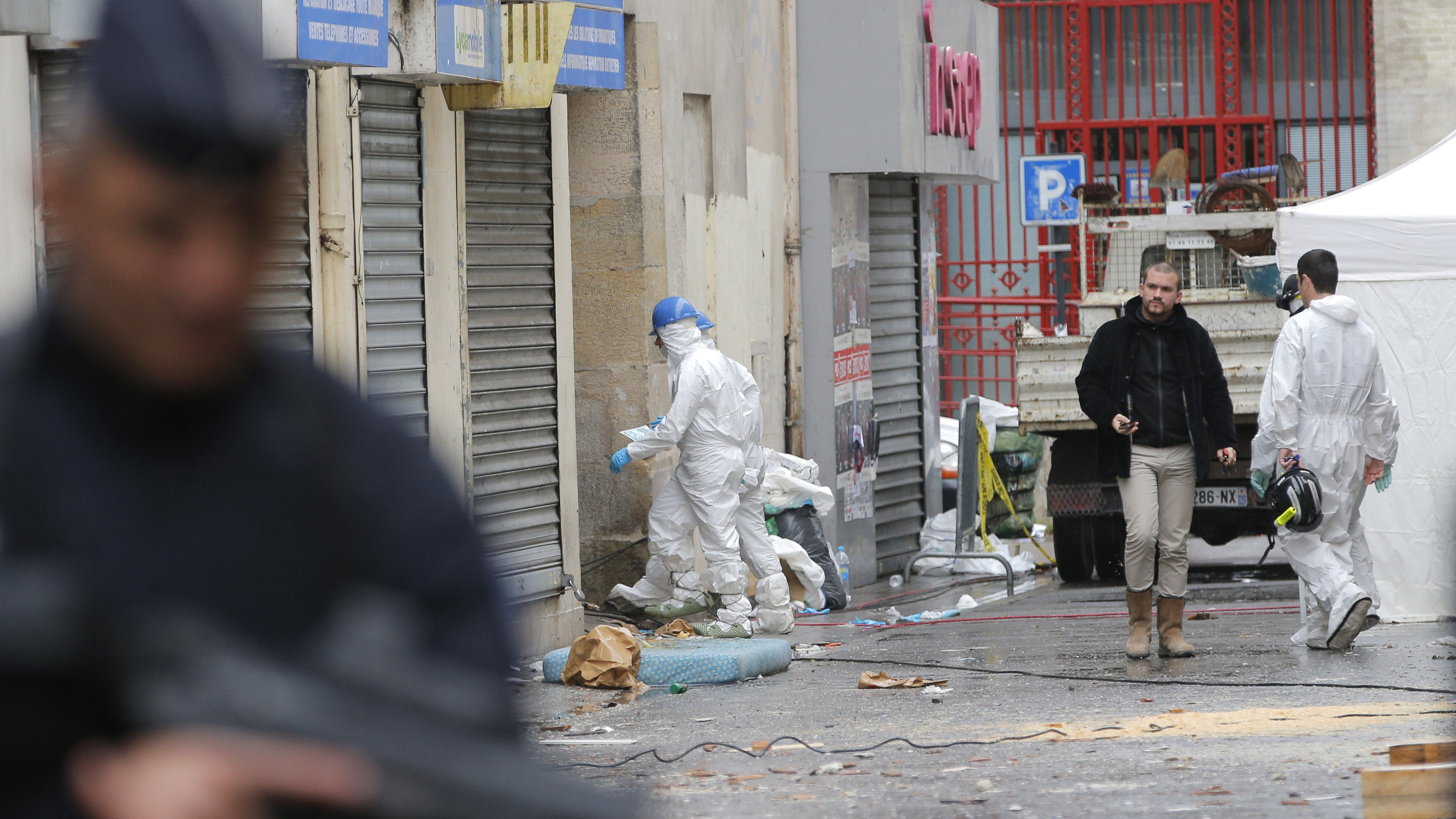 Investigating police officers enter the building of Wednesday's raid on an apartment in Paris suburb Saint-Denis, Thursday Nov.19, 2015.