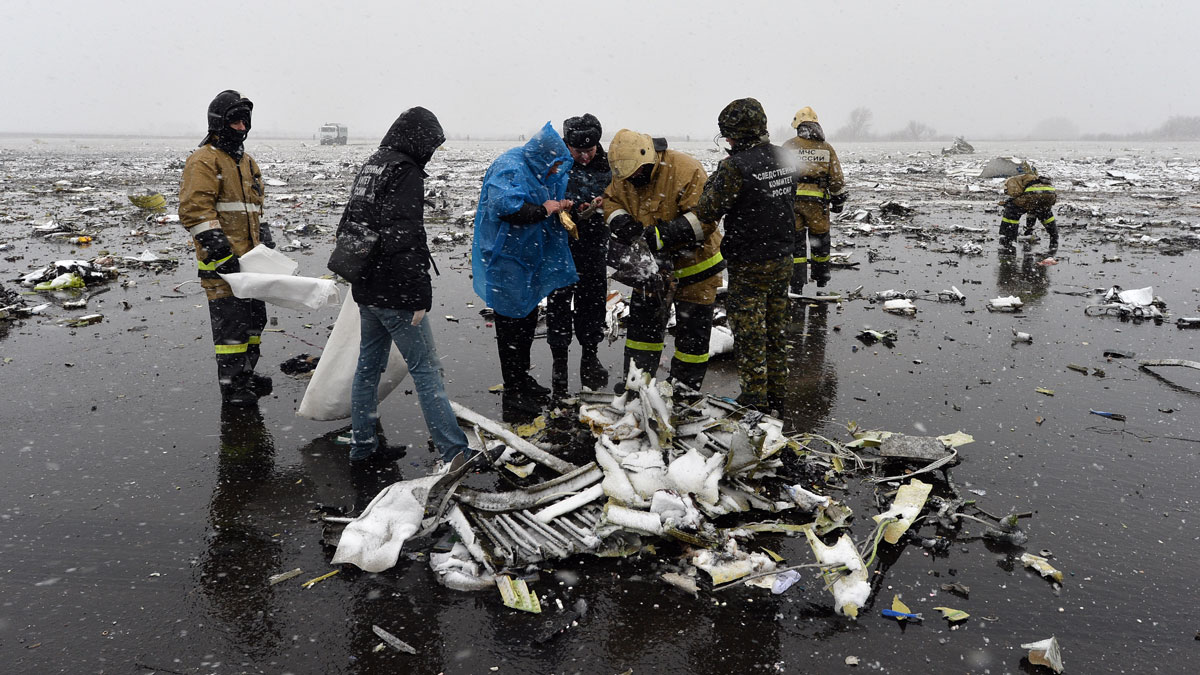 Russian emergency rescuers and forensic investigators work on the wreckage of the flydubai passenger jet which crashed, killing all 62 people on board as it tried to land in bad weather in the city of Rostov-on-Don on March 19, 2016. The plane, which came from Dubai, was making its second attempt to land when it missed the runway, erupting in a huge fireball as it crashed, leaving debris scattered across a wide area. The ministry said more than 700 rescuers and 100 vehicles were combing the area in driving wind and snow where the wreckage was strewn, with investigators confirming one of the plane's black boxes had been retrieved.