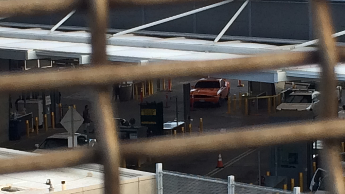 The two people found not breathing at the San Ysidro Port of Entry were inside the trunk of this orange vehicle, as seen here from a pedestrian bridge near the border crossing.