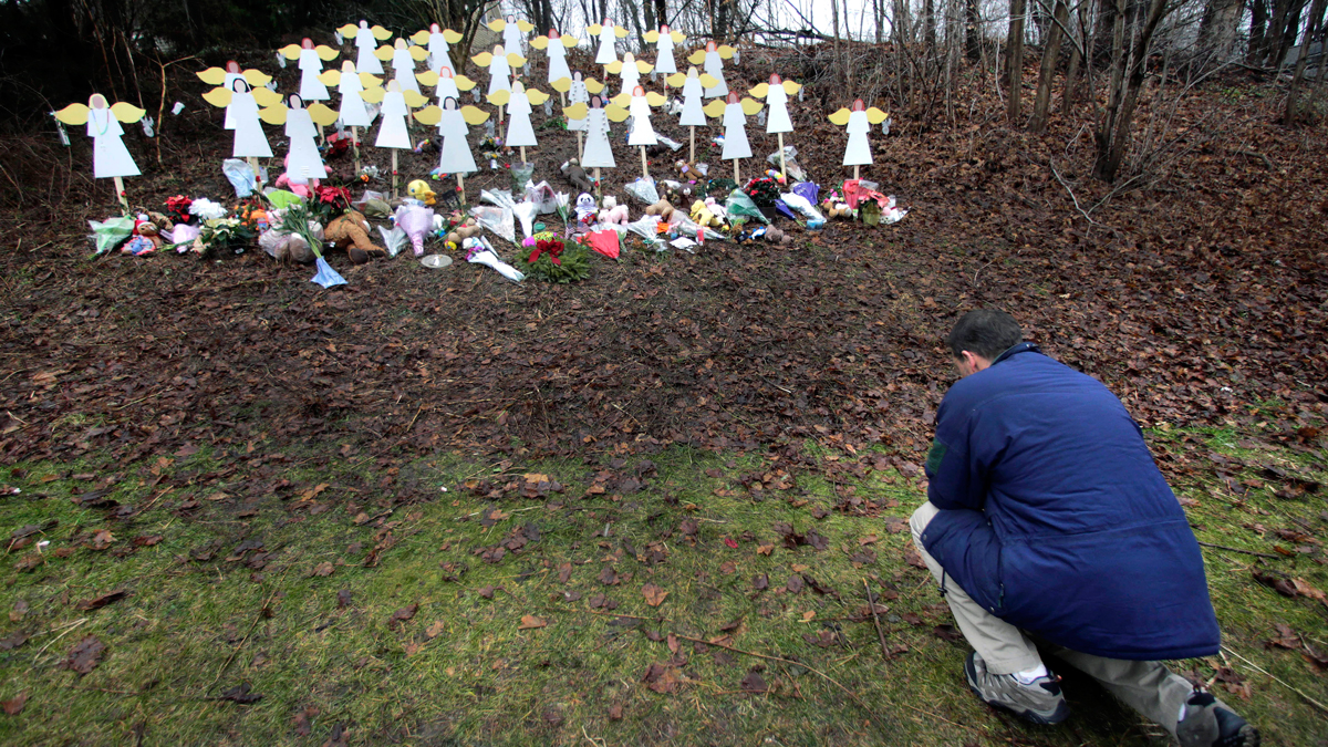 FILE - In this Dec. 18, 2012, file photo, Robert Soltis, of Newtown, Conn., pauses after making the sign of the cross at a memorial to Sandy Hook Elementary School shooting victims in Newtown.