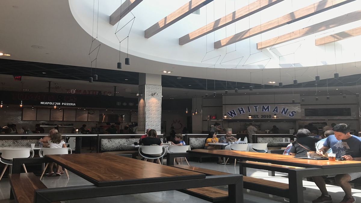 Mall-goers eat in the Westchester Mall's newly-renovated food court August 13, 2017, in White Plains, New York.