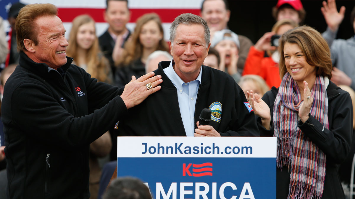 Republican presidential candidate, Ohio Gov. John Kasich, center, steps up to the podium in front of his wife Karen, right, after being introduced by former California Gov. Arnold Schwarzenegger during a campaign rally Sunday, March 6, 2016, in Columbus, Ohio. Schwarzenegger is throwing his support to Gov. John Kasich in the presidential contest.