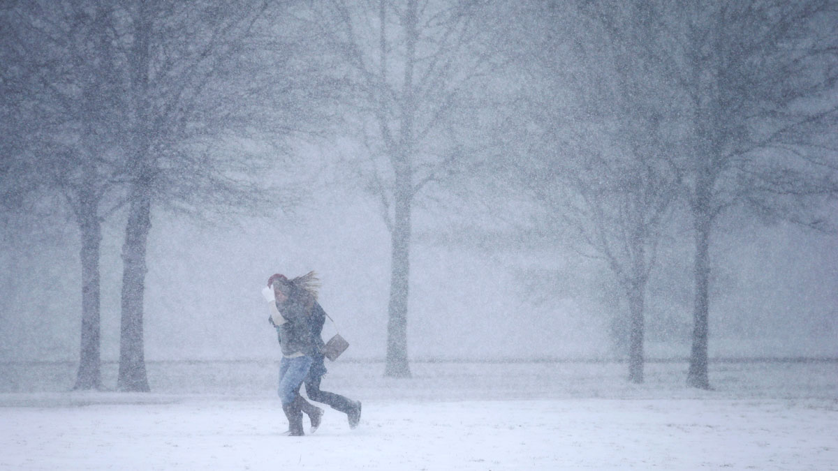 In this Feb. 9, 2016, file photo, two women run through a snow flurry in Nashville, Tennessee.