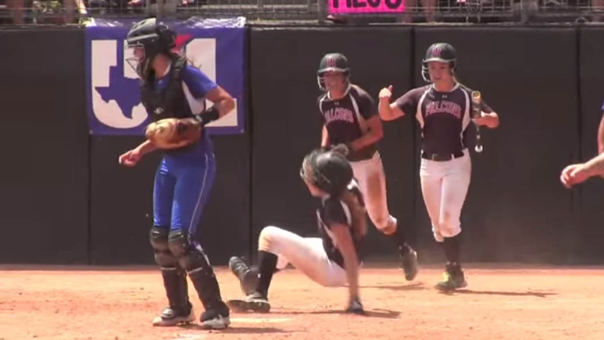 Needville catcher Megan Crosby throws an elbow into an unwitting base runner from Huffman Hargrave, knocking her off her feet, during the Texas 4A softball championship on Saturday, June 6, 2015.