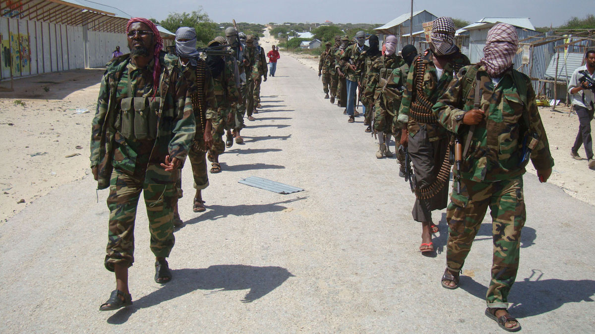 Members of Somalia's al- Shabab militant group patrol on foot on the outskirts of Mogadishu on March, 5, 2012. The group claimed responsibility for twin attacks that killed 20 people in the country's Puntland region.
