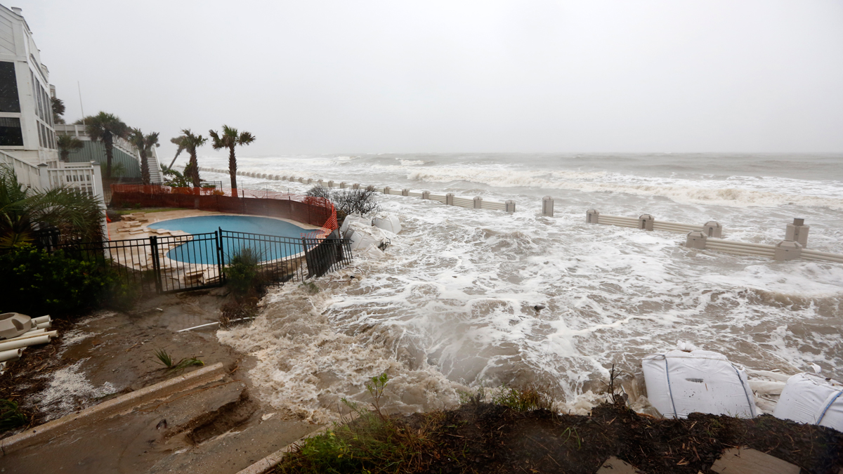 Waves crash over an experimental sea wall to protect homes during high tide on the Isle of Palms Saturday, Oct. 3, 2015. The South Carolina coast is getting hammered with historic rains along with an unusual lunar high tide causing flooding all over the state. Traditional sand bags are seen at bottom of photo.